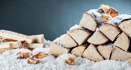 Photo for Woodpile with stacked logs and kindling buried in fresh winter snow in a close up view conceptual of natural biofuels for heating - Royalty Free Image