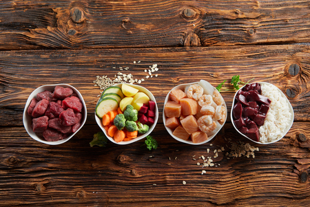 Foto de Bowls of fresh ingredients for a healthy animal diet for your dog or cat with raw beef, liver, chicken, vegetables, grains and rice on a rustic wood background with copy space - Imagen libre de derechos