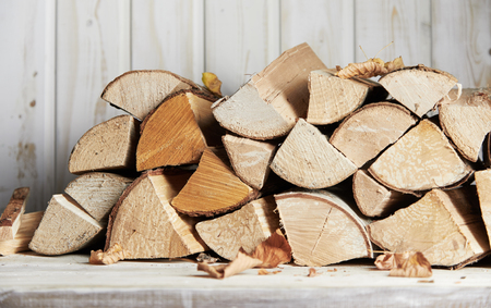 Photo for Stacked woodpile of dried wooden logs ready for heating the house or a barbecue in autumn in a close up view outdoors - Royalty Free Image