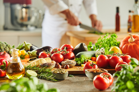 Foto de Cutting board completely covered with assorted food and man in chef outfit chopping herbs in background - Imagen libre de derechos