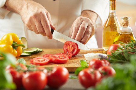 Foto de Chef slicing fresh tomatoes for a salad in a low angle view of the knife and chopping board over assorted fresh vegetable ingredients - Imagen libre de derechos