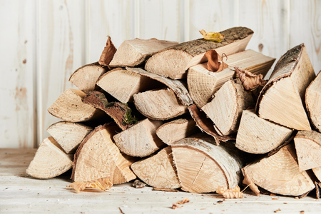 Photo for Woodpile of chopped and split firewood with autumn leaves in front of an old white painted wall outdoors - Royalty Free Image