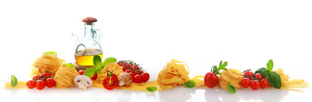 Foto de Panorama banner of fresh homemade Italian pasta with tomatoes, basil and olive oil on a reflective white surface with copyspace - Imagen libre de derechos