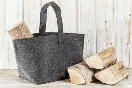 Photo for Rustic textile bag with chopped firewood for a barbecue or winter heating in front of a white painted wooden wall with copy space - Royalty Free Image