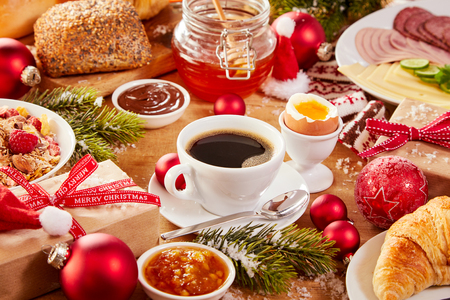 Photo pour Christmas Intercontinental breakfast table with an assortment of tasty fresh food, coffee, gifts and colorful red decorations sprinkled with winter snow - image libre de droit