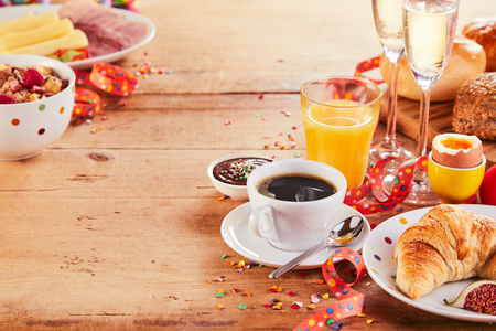 Photo pour Festive carnival breakfast borders with streamers, confetti and champagne on a wooden table - image libre de droit
