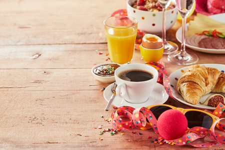 Photo pour Carnival breakfast border with party accessories amidst a tasty spread of cereal, coffee, cheese, meat, egg, orange juice and croissant, copy space on wood - image libre de droit