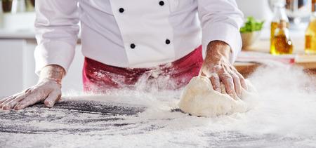 Photo pour Adult man sliding large chunk dough along table to pick up white powdery flour with kitchen in background - image libre de droit