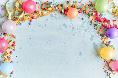 Foto de Carnival, festival or birthday balloon background with colorful party streamers, candy and confetti making a border on a blue background with copy space - Imagen libre de derechos