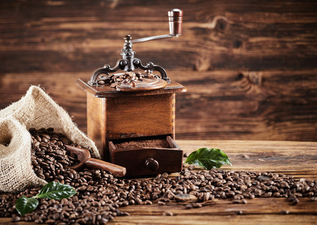 Foto de Rustic wooden coffee mill with beans spilling from a burlap bag onto an old weathered wood table with copy space - Imagen libre de derechos