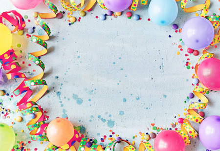 Photo pour Multicolored carnival or birthday background on blue with a frame of colorful party balloons, streamers, confetti and candy around central copy space - image libre de droit