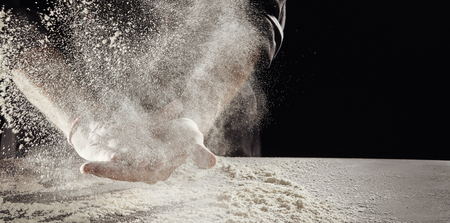 Photo for Cloud of flour caused by unidentified man cleaning off hands hands over table already covered in white powder - Royalty Free Image