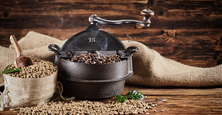 Foto de Old vintage cast iron coffee roaster and raw beans in burlap sacks spilling onto a rustic wooden counter in a coffee house in a panorama banner - Imagen libre de derechos