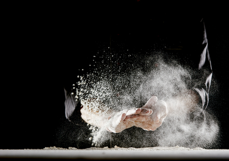 Photo pour Powdery flour flying into air as man in black chef outfit wipes off his hands over white table covered in flour - image libre de droit