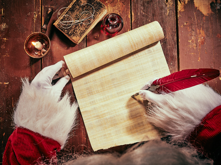 Foto de Gloved hands of Father Christmas writing on a blank vintage parchment scroll with copy space with a feather quill by the light of a burning candle in a close up overhead view - Imagen libre de derechos