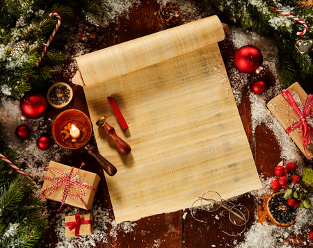Foto de Blank Christmas scroll surrounded by fresh pine foliage and with decorations, winter snow and wax seal in a flat lay still life - Imagen libre de derechos