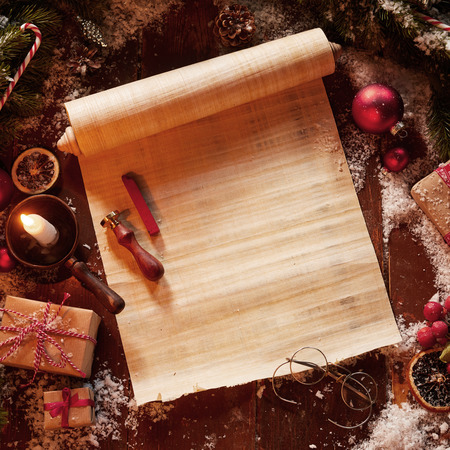 Foto de Christmas vintage scroll with spectacles, gifts and decorations surrounded by pine foliage and a burning candle - Imagen libre de derechos