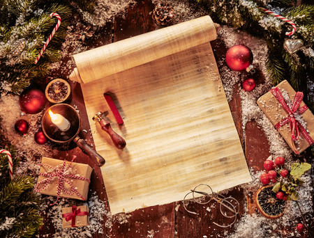 Foto de Parchment scroll with Christmas decorations and olden day circular reading glasses lit by candlelight with copy space on the paper for your holiday greeting - Imagen libre de derechos