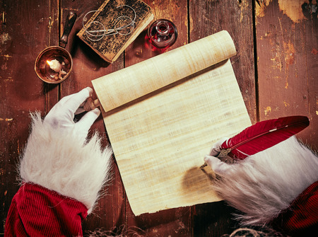 Foto de Costumed hands of Santa Claus writing a Christmas letter or greeting on a blank parchment scroll by candlelight on a vintage rustic table viewed from above - Imagen libre de derechos