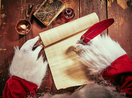 Foto de Hands of Santa Claus writing a Christmas letter on a vintage scroll with a red quill pen by candlelight on an old rustic wooden table - Imagen libre de derechos