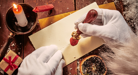 Photo pour Santa Claus sealing an envelope with a decorative red wax seal showing his face in a close up of his hands lit by candlelight - image libre de droit