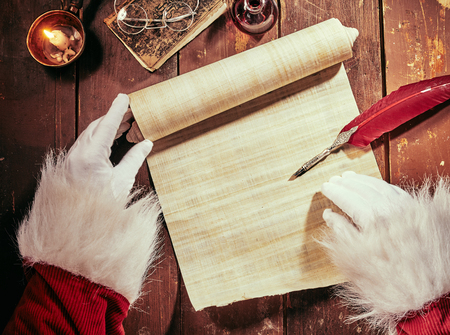 Foto de Gloved hands of Father Christmas writing on a vintage parchment scroll with a feather quill pen by candlelight with copy space on the paper - Imagen libre de derechos