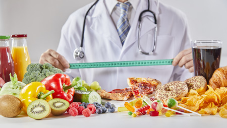 Photo pour Doctor in coat with long stethoscope holding ruler over table with random assortment of healthy and unhealthy food - image libre de droit