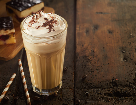 Photo pour High glass of frothy cappuccino coffee with chocolate topping served with cake and candies on old dark wooden table. Copy space - image libre de droit