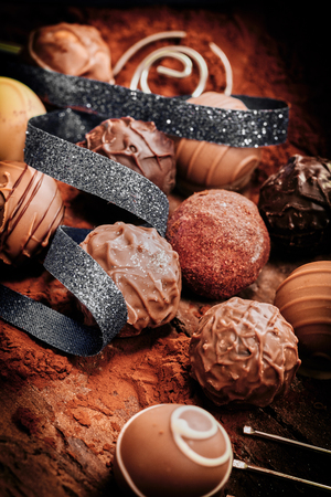Photo pour Assorted luxury handmade chocolate bonbons decorated with a coiled ribbon on a bed of cacao or chocolate powder - image libre de droit