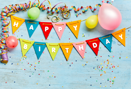 Foto de Happy Birthday bunting background with colorful triangular flags, party balloons, streamers and confetti on a blue wood background with copy space - Imagen libre de derechos