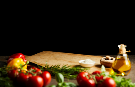 Photo pour Fresh cooking ingredients around a wooden board with vegetables, herbs condiments and olive oil against a black background with copy space - image libre de droit