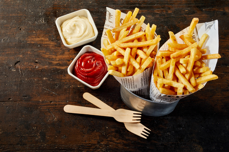 Photo pour Two takeaway portions of fried potato chips or French fries in paper cones standing in a can with ketchup and mayonnaise on wood - image libre de droit