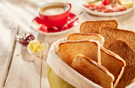 Photo pour Freshly made crunchy toasts, served in fabric bag with coffee and butter blurred in background on wooden table - image libre de droit