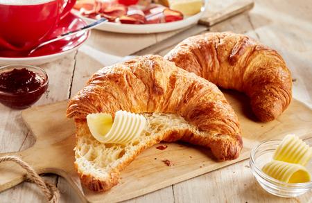 Foto de Sliced fresh baked croissant served with butter curls on wooden cutting board - Imagen libre de derechos