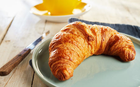 Foto de Fresh baked flaky French croissant served on plate with knife on wooden table - Imagen libre de derechos