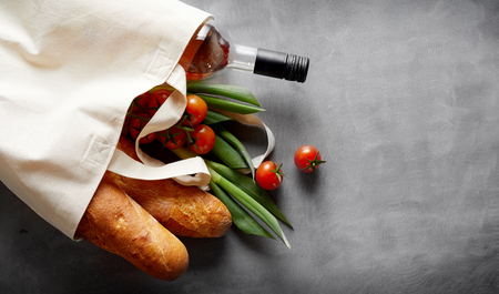 Photo pour Eco-friendly reusable textile bag with groceries and wine spilling out onto a slate background with copy space - image libre de droit