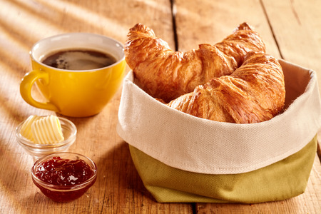 Photo for Freshly baked flaky croissants served in fabric bag with butter curls, jam and cup of coffee on rustic wooden table - Royalty Free Image
