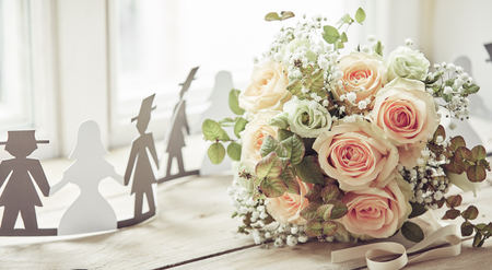 Foto de Bride and groom cut out shapes decorations and beautiful bridal bouquet of pale pink roses, on wooden surface of window sill - Imagen libre de derechos