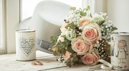 Photo pour Bright composition for marriage day with wedding rings, bridal bouquet of pink roses, groom's white hat and cans with decorations and wishes on bright window sill - image libre de droit