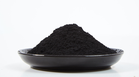 Photo pour A pile of powdered charcoal on black plate, viewed from the side against white background - image libre de droit