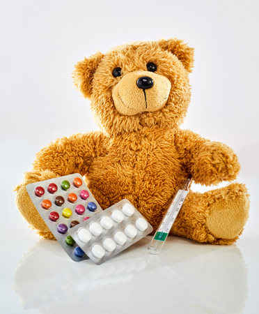 Photo pour Toy bear with medicine, thermometer and colorful pills in blister pack, sitting on glossy surface against white background. Viewed from its front. Pediatrician office and children health concept - image libre de droit