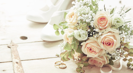 Foto de Marriage day composition with shoes, pink roses flowers bridal bouquet and wedding rings viewed from high angle on wooden background - Imagen libre de derechos