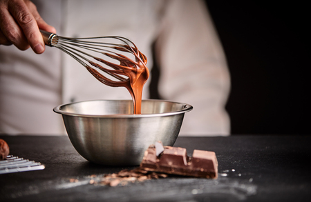 Photo for Chef whisking melted chocolate in a stainless steel mixing bowl using an old vintage wire whisk in a close up on his hand - Royalty Free Image