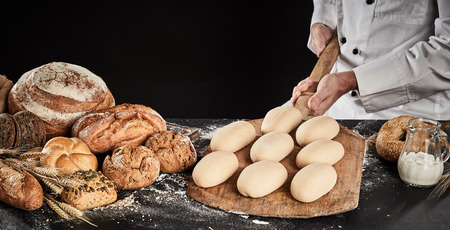 Foto de Raw dough for loaves of bread on a wooden paddle ready to be placed in the oven for baking held in the hands of a chef or baker - Imagen libre de derechos