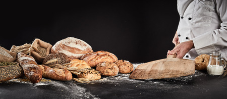 Photo for Baker placing an empty wooden paddle on a table ready fore placing dough for baking with a display of speciality bread alongside - Royalty Free Image