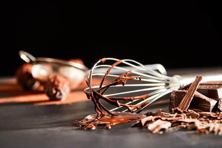 Photo for Preparing chocolate bonbons with an old whisk to beat the melted chocolate ingredient lying on a kitchen table in a low angle view - Royalty Free Image