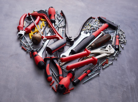 Photo pour Heart shaped arrangement of assorted red hand tools for woodworking on a textured grey in a close up view - image libre de droit