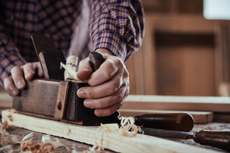 Photo pour Carpenter or joiner planing a plank of wood smoothing the surface in a close up view on his hands and the tool on a workbench - image libre de droit