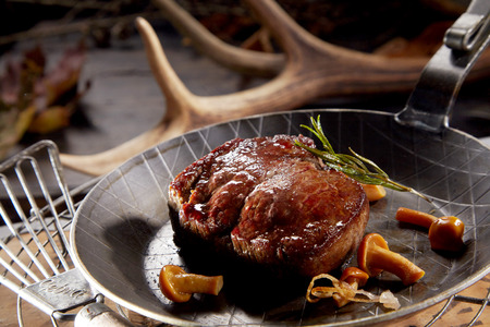 Foto per Thick juicy grilled wild venison steak served in a skillet with forest mushrooms and rosemary against a backdrop of shed antlers form deer - Immagine Royalty Free