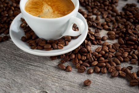 Foto de Coffee background still life with roasted beans and a cropped view of a cup of freshly brewed frothy espresso coffee with corner copy space on rustic wood - Imagen libre de derechos